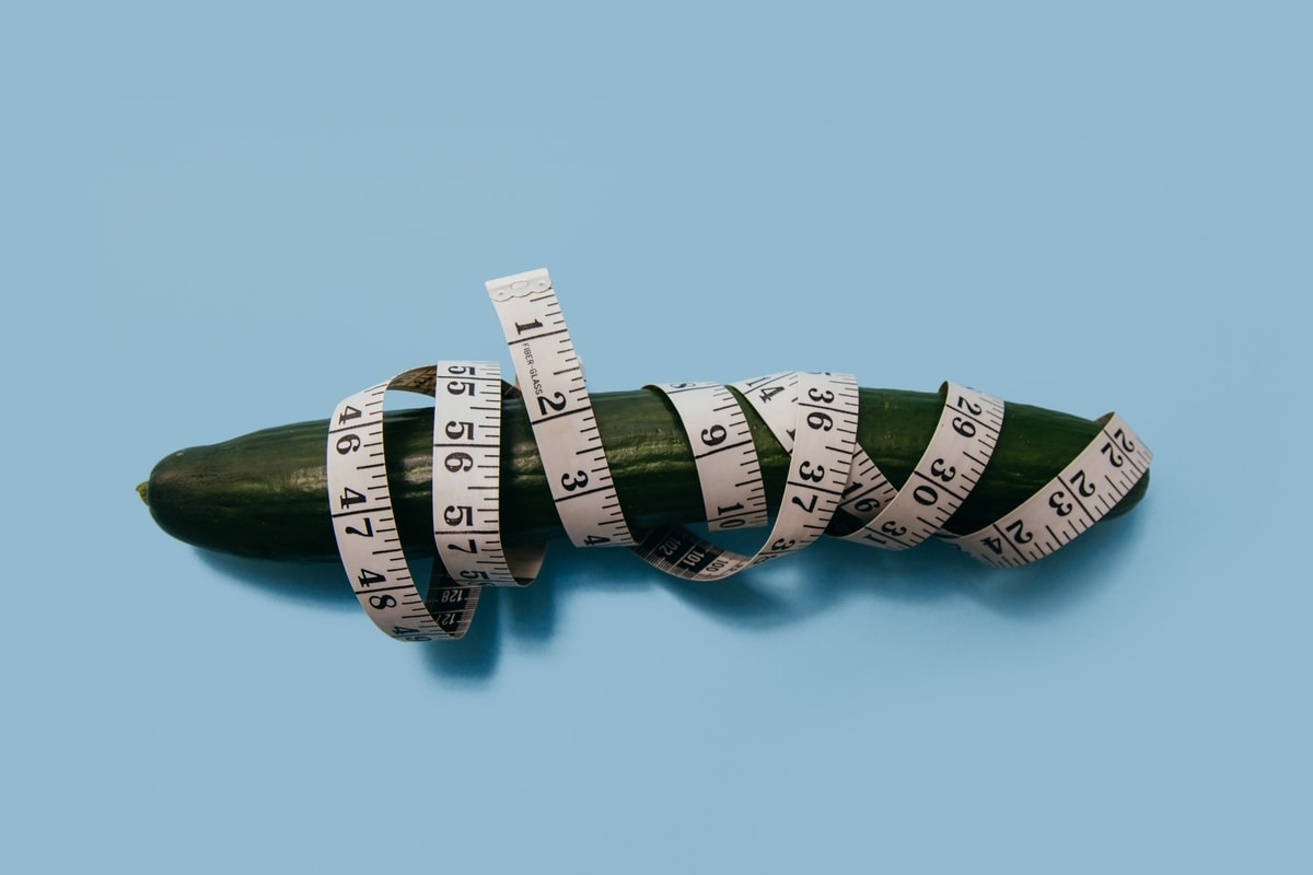 Cucumber on a blue background and measuring tape wrapped around it