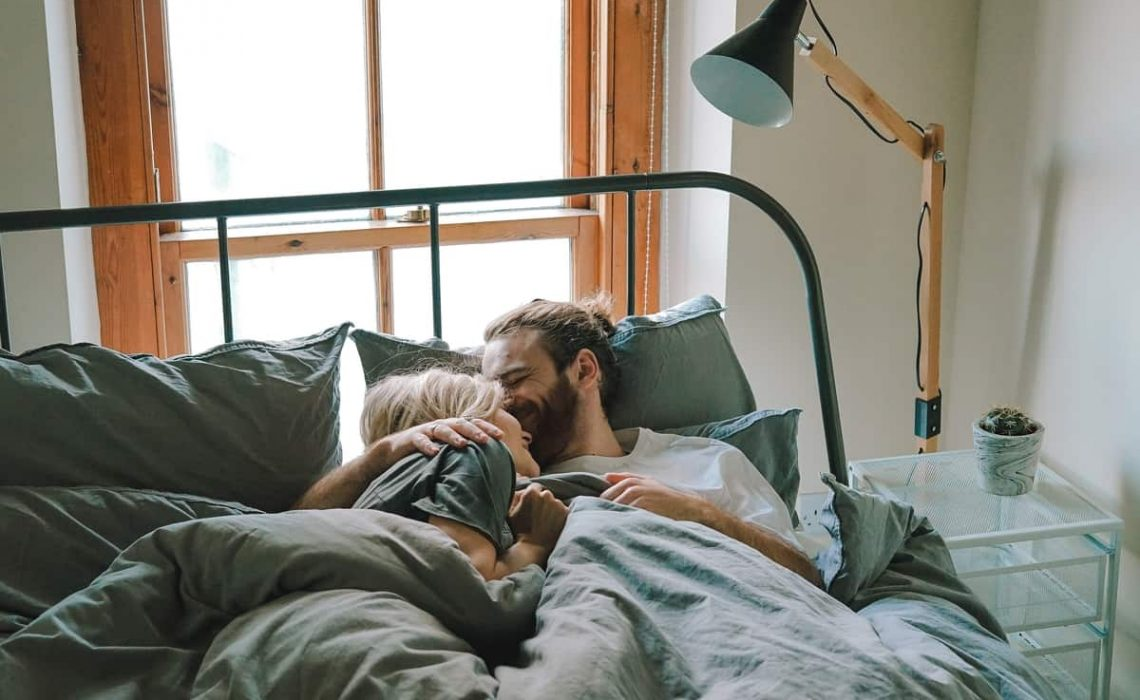 Man is kissing his girlfriend on the forehead (in bed)